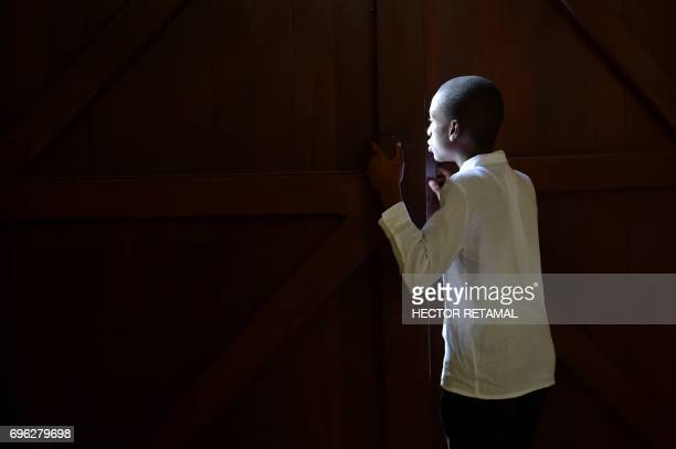 TOPSHOT A boy looks between the doors of the St Pierre Church in the commune of Petion Ville PortauPrince on June 15 while waiting for the arrival of...