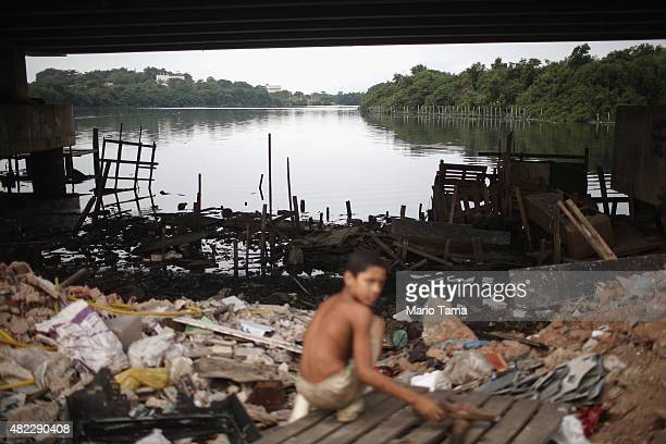 A boy looks for items to recycle along the polluted Cunha canal which flows into the notoriously polluted Guanabara Bay site of sailing events for...