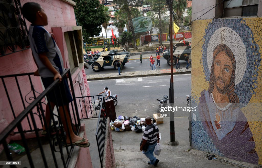 A boy (L) looks from a balcony as Army tanks and supporters of Venezuelan President Hugo Chavez take to the streets to conmemorate the 1992 failed coup led by Chavez, who was an army lieutenant colonel, against then president Carlos Andres Perez, in Caracas, on February 4, 2013. Ailing President Hugo Chavez, who had cancer surgery in December, is doing much better and recovering, Cuban leader Fidel Castro said in remarks published Monday. AFP PHOTO/Leo RAMIREZ