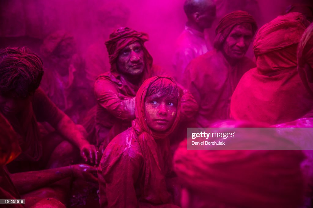 A boy looks on as Hindu devotees play with color during Lathmaar Holi celebrations on March 21, 2013 in the village of Barsana, near Mathura, India. The tradition of playing with colours on Holi draws its roots from a legend of Radha and the Hindu God Krishna. It is believed that young Krishna was jealous of Radha's fair complexion since he himself was himself very dark. After questioning his mother Yashoda on the darkness of his complexion, Yashoda, teasingly asked him to colour Radha's face in which ever colour he wanted. In a mischievous mood, Krishna applied colour on Radha's face. The tradition of applying color on one's beloved is being religiously followed till date.