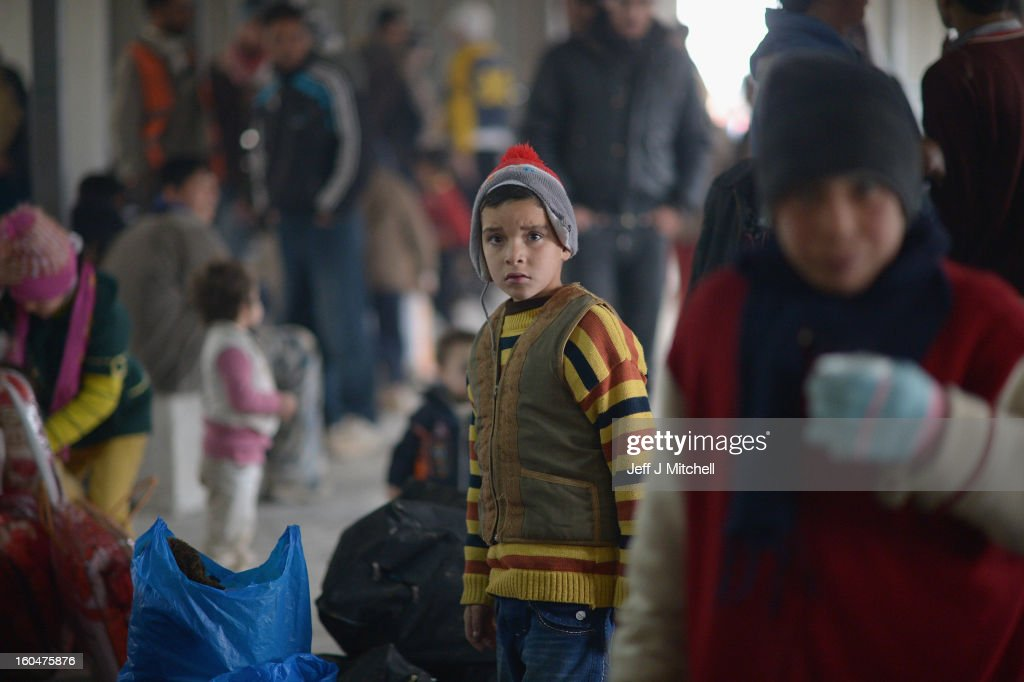 ZA'ATARI, JORDAN - FEBRUARY 01: A boy looks on as new Syrian refugees arrive at the International Organization for Migration at the Za'atari refugee camp on February 1, 2013 in Mafrq, Jordan. Record numbers of refugees are fleeing the violence and bombings in Syria to cross the borders to safety in northern Jordan and overwhelming the Za'atari camp. The Jordanian government are appealing for help with the influx of refugees as they struggle to cope with the sheer numbers arriving in the country.
