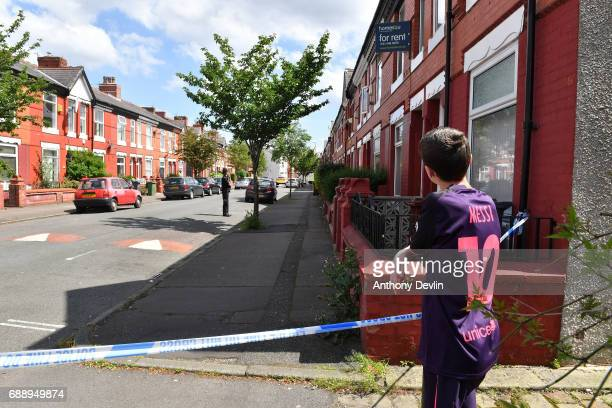 A boy looks on as Police attend the scene of a raid in the Moss Side area as part of their ongoing investigation following the terror attack earlier...