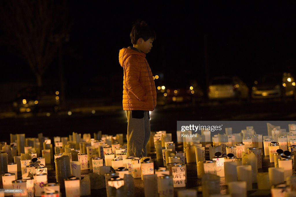 A boy looks on during a ceremony to commemorate the victims on March 11 2015 in Minamisoma Fukushima prefecture Japan On March 11 Japan commemorates...