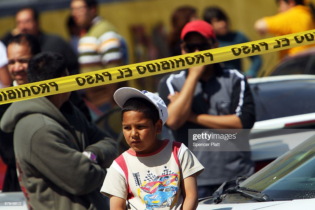 A boy looks out at a murder scene in which two men lay dead on March 22, 2010 in Juarez, Mexico. Both men, who were 18 and 34 years of age, were shot by a group of teenagers. The border city of Juarez, Mexico has been racked by violent drug related crime recently and has quickly become one of the most dangerous cities in the world to live. As drug cartels have been fighting over ever lucrative drug corridors along the United States border, the murder rate in Juarez has risen to 173 slayings for every 100,000 residents. President Felipe Calderon�s strategy of sending 7000 troops to Juarez has not mitigated the situation. With a population of 1.3 million, 2,600 people died in drug-related violence last year and 500 so far this year, including two Americans recently who worked for the U.S. Consulate and were killed as they returned from a children�s party.