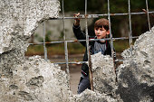 A boy looks out from a wall damaged during heavy fighting on September 10 2014 in Alovaisk Ukraine Alovaisk which is about an hour outside of the...