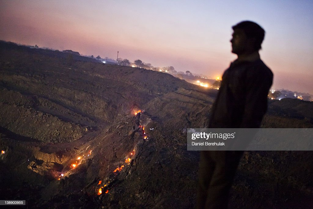 A boy looks out over an open-cast coal mine as the glowing embers of an underground coal fire are seen below in the village of Guhanwadi on February 11, 2012 near Jharia, India. Villagers in India's Eastern State of Jharkhand scavenge coal illegally from open-cast coal mines to earn a few dollars a day. Claiming that decades old underground burning coal seams threatened the homes of villagers, the government has recently relocated over 2300 families to towns like Belgaria. Villagers claim they were promised schools, hospitals and free utilities for two years, which they have not received. As the world's power needs have increased, so has the total global production of coal, nearly doubling over the last 20 years according to the World Coal Association.