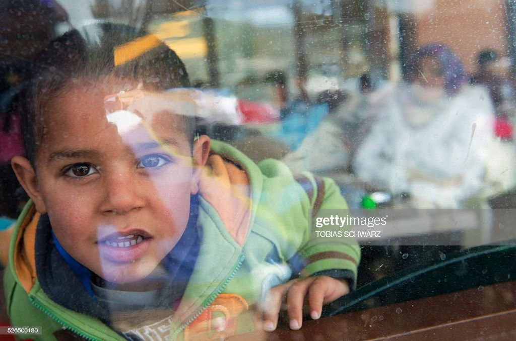 A boy looks out through a plastic window at a makeshift camp for migrants and refugees near the village of Idomeni not far from the Greek-Macedonian border on April 30, 2016. Some 54,000 people, many of them fleeing the war in Syria, have been stranded on Greek territory since the closure of the migrant route through the Balkans in February. / AFP / TOBIAS