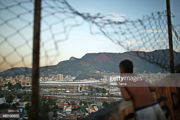 A boy looks out while kids fly kites in the Mangueira community or 'favela' which overlooks the famed Maracana Stadium on June 5 2014 in Rio de...
