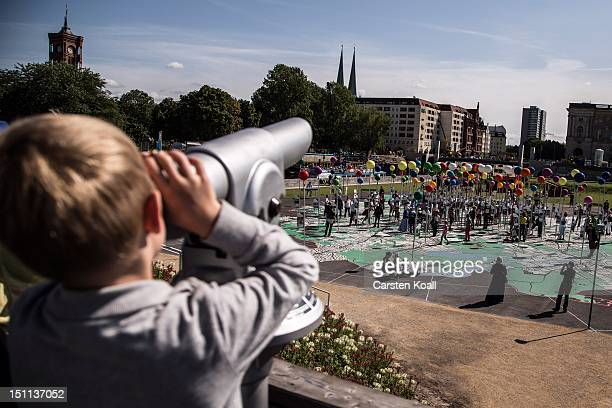 A boy looks through a telescope towards a giant map of Berlin in 1775th scale complete with giant coloured pins marking sites of historical...