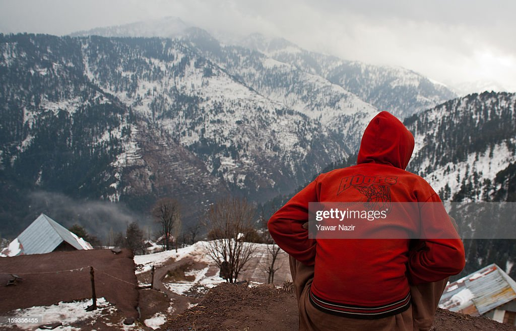 A boy looks towards snow covered mountains of Pakistan administered Kashmir Churunda village on January 12, 2013, northwest of Srinagar, the summer capital of Indian Administered Kashshmir, India. The village with a population of a little over 12,000 people has been bearing the brunt of cross-fire between nuclear rivals India and Pakistan. Last week a Pakistan solider was killed across the Line of Control (LOC), a military line that divides Indian-administered Kashmir from the Pakistan-administered Kashmir at this village. People living along the LoC have continually been at risk due to hostility between the armies of the two rival nations. Last year, in November, three people, including a pregnant woman, had died after a shell fired from Pakistan landed on one of the houses in the village. Tension between Pakistan and India has escalated after a fresh skimirish along the border. Both countries have summoned each other's envoy to protest against unacceptable and unprovoked' attacks.