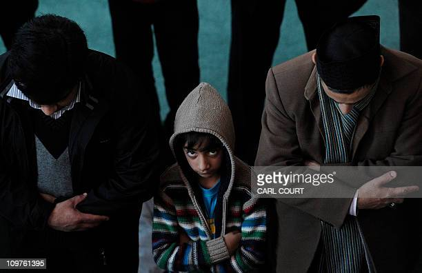 A boy looks up as he and other Muslims take part in Friday prayers in Baitul Futuh Mosque in south London on February 18 as they attend a Unite...
