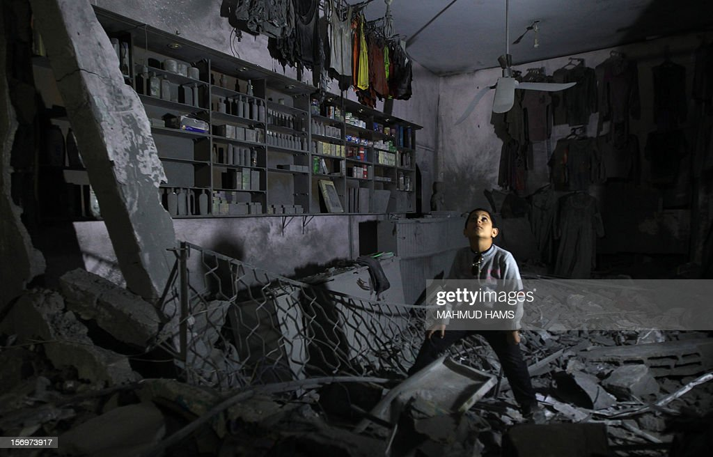 A boy looks up as he walks in the rubble of a destroyed shop in Beit Lahia, in the northern Gaza Strip, on November 26, 2012, following a truce last week between Israel and Hamas that ended eight days of conflict in which 166 Palestinians and six Israelis were killed.