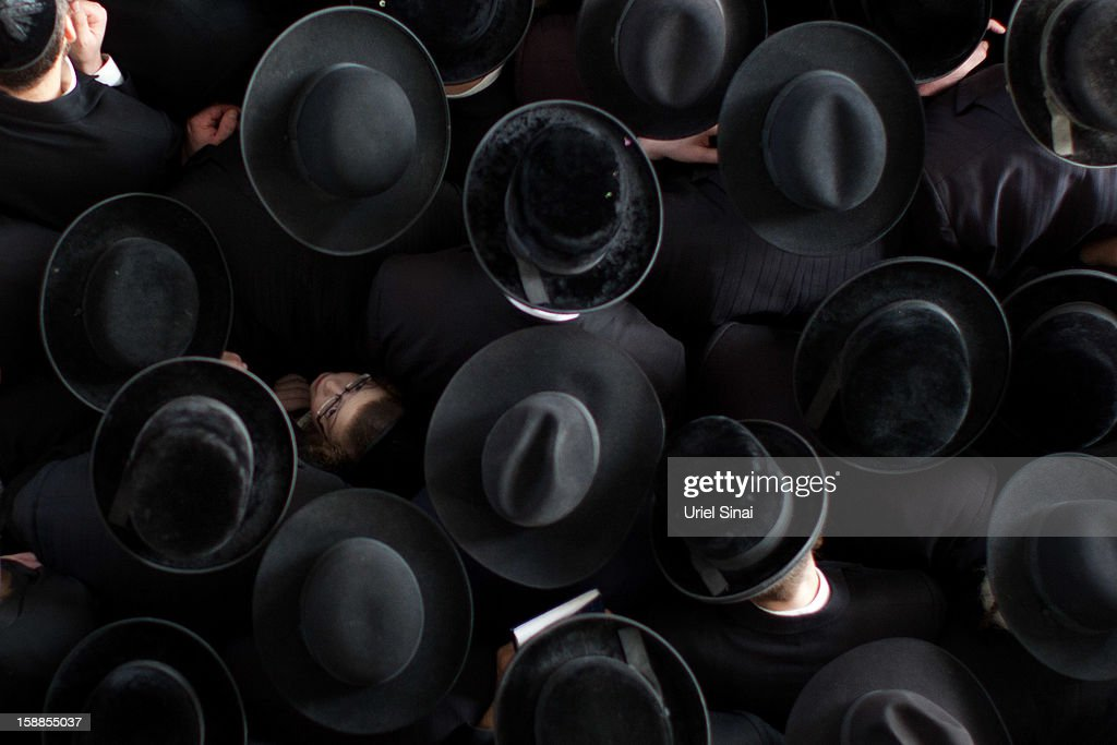 A boy looks up as Ultra Orthodox Jewish men pray next to the body of Rabbi Abraham Jacob Friedman of Sadigura Hasidic dynasty during his funeral on January 01, 2013. in Bnei Brak, Israel. The Rabbi was the leader of the Sadigura Hasidic dynasty in Bnei Brak and died at the age of 84.