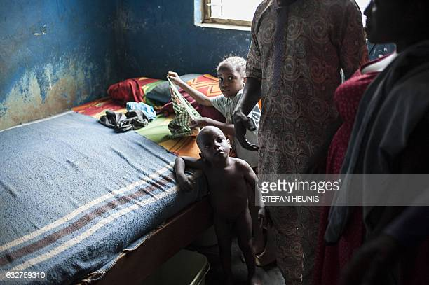 A boy looks up at his parents in their one bedroom accommodation on January 6 2017 in Lagos Nearly two years after taking office Nigeria's President...