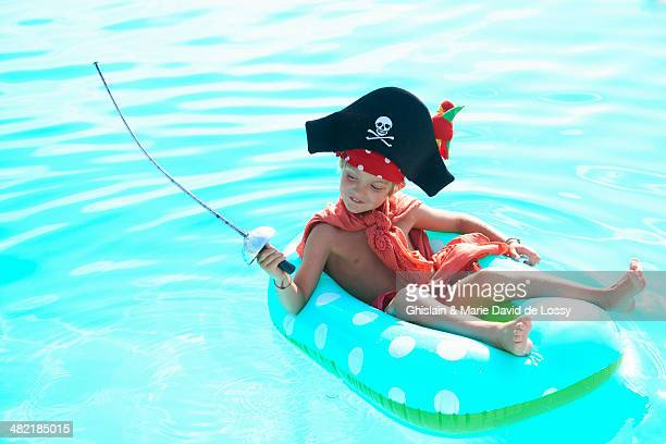 Boy lounging on rubber ring in pool dressed up as a pirate