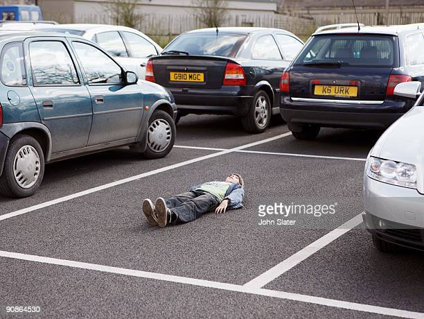 Boy lying down in parking lot