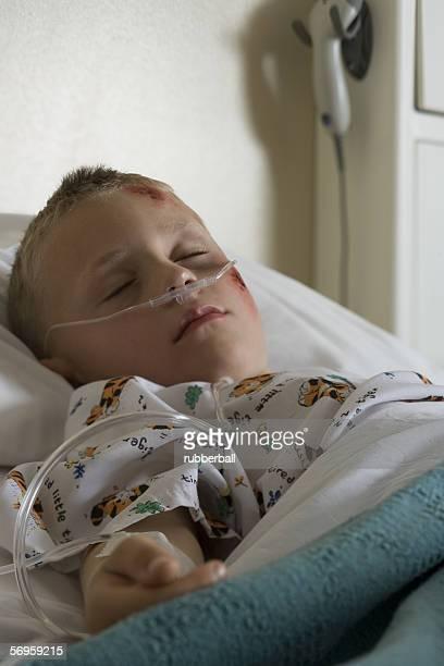 Boy lying in a hospital bed breathing through a tube