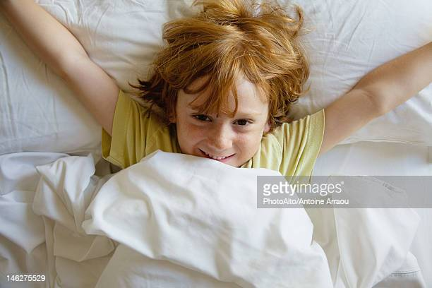 Boy lying in bed with arms outstretched
