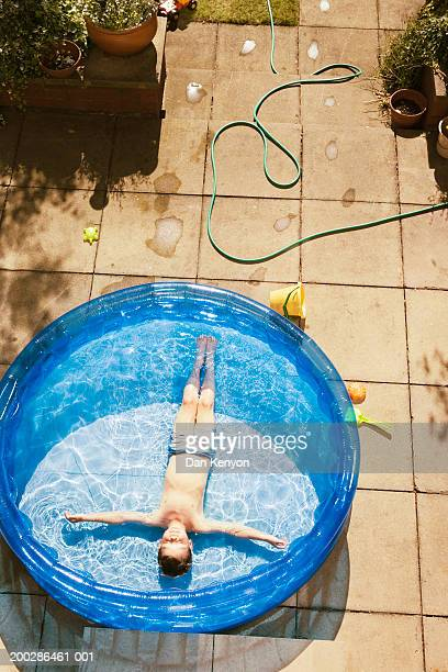 Boy (4-6) lying in paddling pool, eyes closed, elevated view