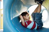 Boy lying in playground tunnel
