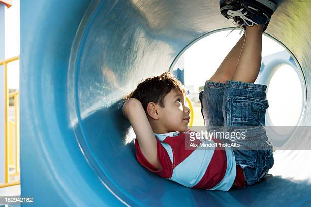 Boy lying in playground tunnel
