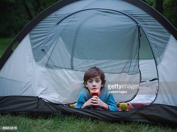 Boy lying in tent with flashlight