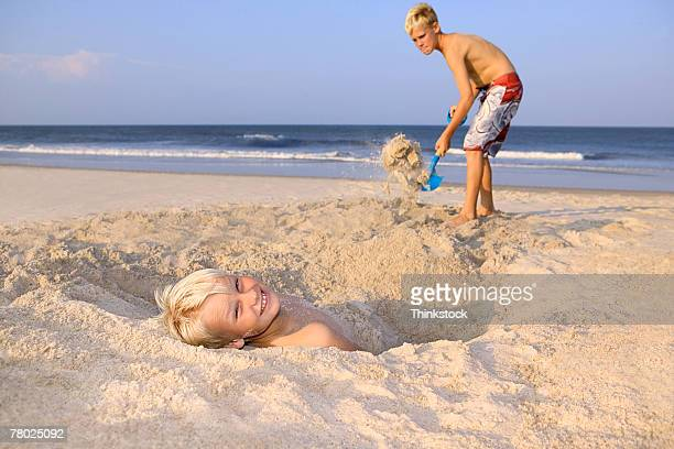A boy lying in the sand looks back to the viewer as another boy buries him with sand