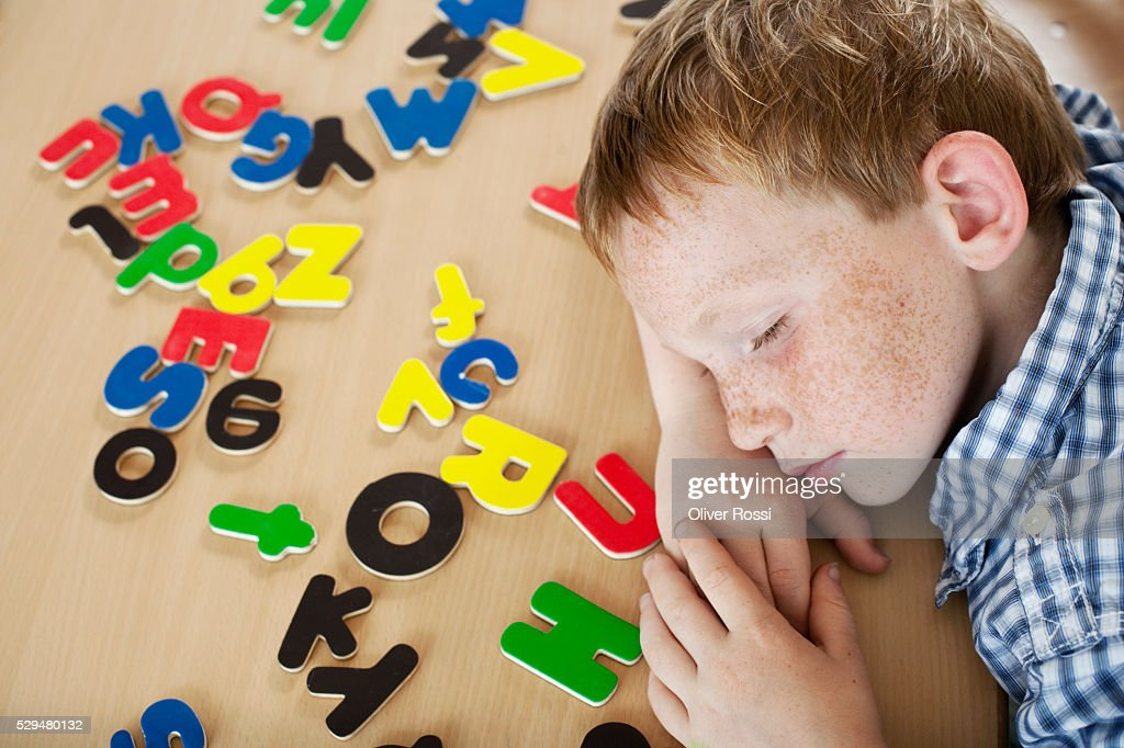 Boy lying next to alphabet letters : Photo