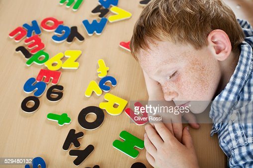 Boy lying next to alphabet letters : Stock-Foto