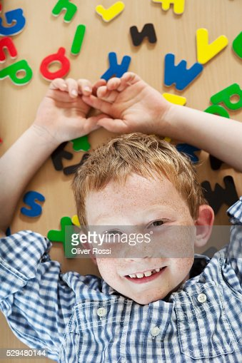 Boy lying next to alphabet letters : Stockfoto