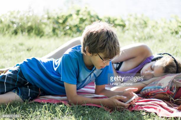 A boy lying on a beach towel looking at his cellphone and a girl lying beside him with headphone
