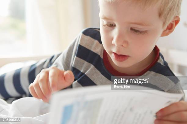 Boy lying on bed reading a book