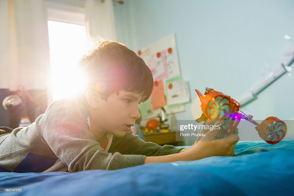 Boy lying on bed with toy