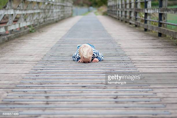 Boy lying on bridge looking down through cracks
