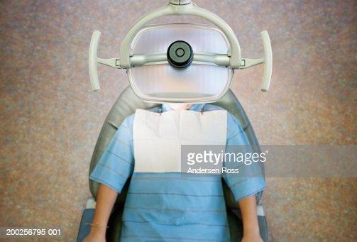 Boy (10-12) lying on dentist's chair, overhead view