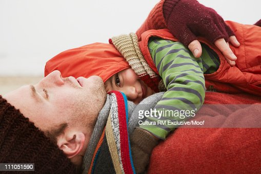 Boy lying on father at beach : Stock Photo
