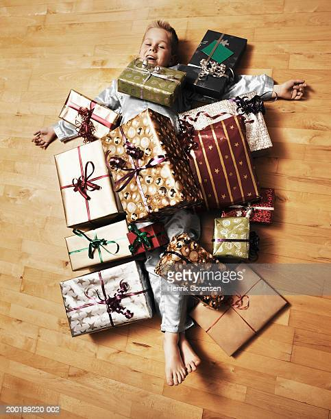 Boy (4-6) lying on floor covered in presents, portrait, smiling