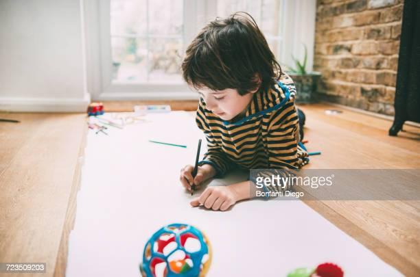 Boy lying on floor drawing on long paper