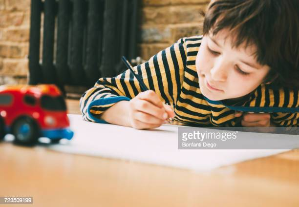 Boy lying on floor drawing on paper
