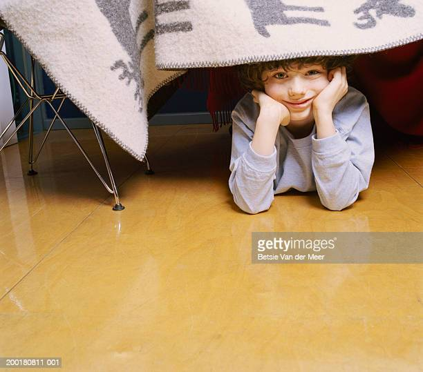 Boy (7-9) lying on floor looking out from under blanket, portrait