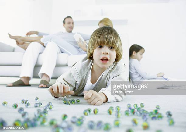Boy lying on floor playing marbles, parents and sister sitting in background