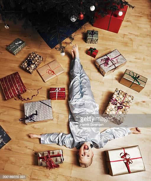Boy (4-6) lying on floor surrounded by Christmas presents, portrait