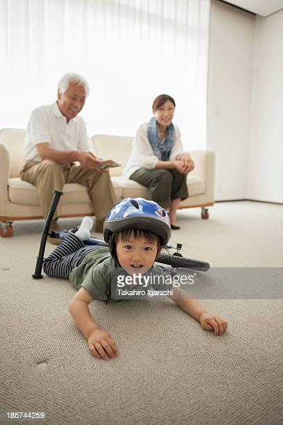 Boy lying on floor with bicycle