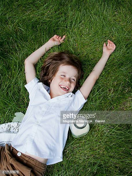 Boy lying on grass laughing