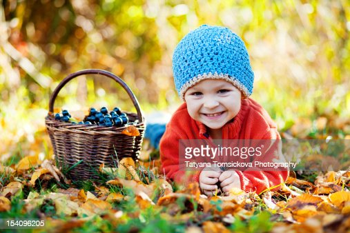Boy lying on grass  with autumn leaves : Stock Photo