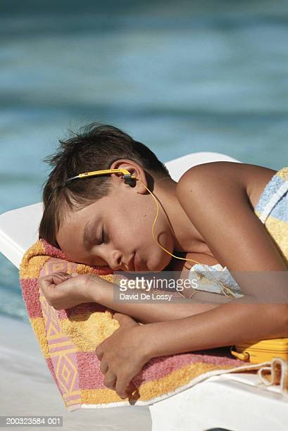 Boy (8-9) lying on lounge chair, listening music
