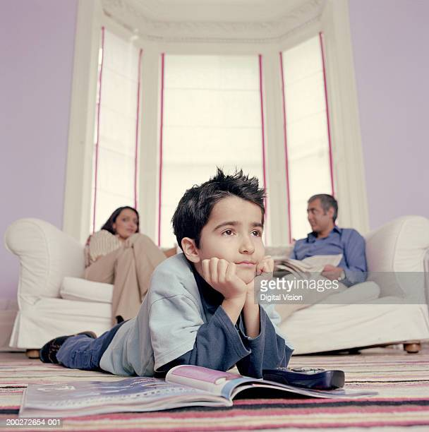 Boy (6-8) lying on mat by magazine, parents on sofa in background