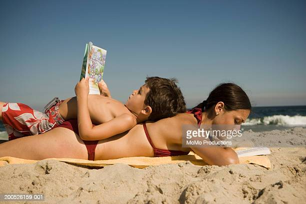 Boy (4-6) lying on mother's back at beach, both reading books