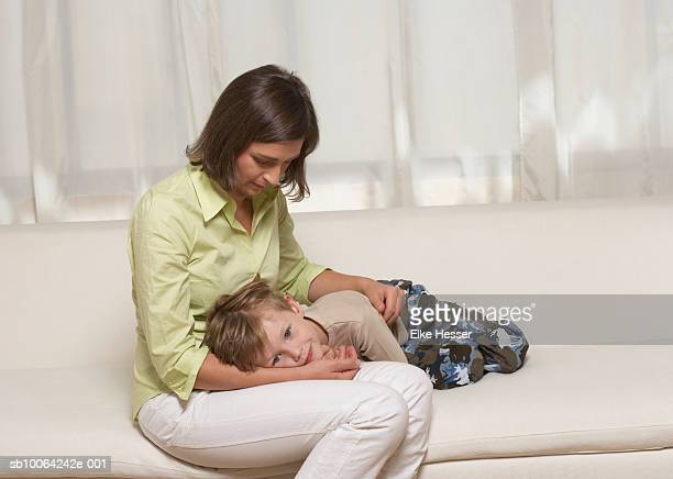 Boy (6-7 years) lying on mothers lap, sitting on couch