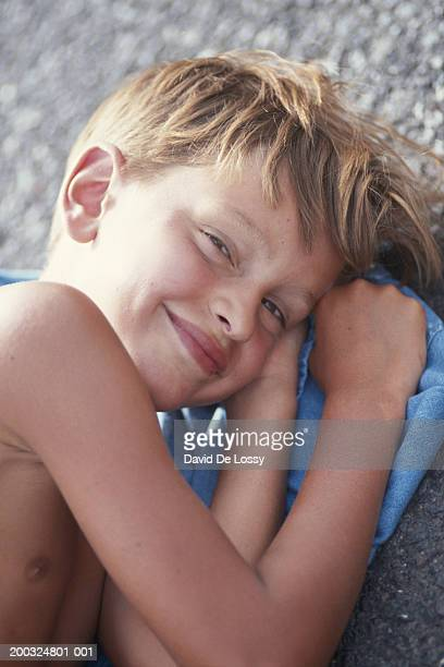 Boy (8-9) lying on side, smiling, elevated view